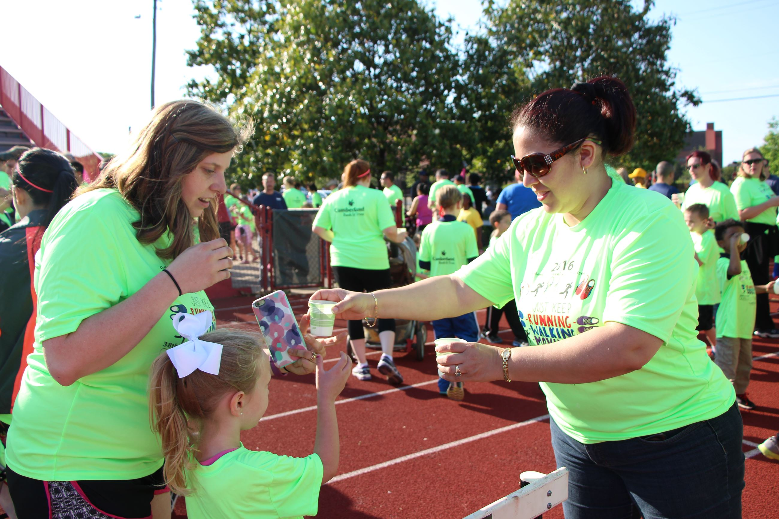 woman handing out cups of beverages at race